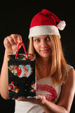 Christmas girl. Christmas blonde girl offer a gift in a bag, black background royalty free stock image