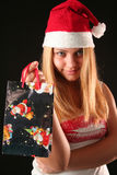 Christmas girl. Christmas blonde girl offer a gift in a bag, black background royalty free stock images