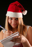 Christmas girl. Christmas blonde girl with pencil and bloc notes thinking and writing royalty free stock photos