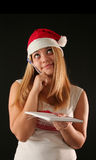 Christmas girl. Christmas blonde girl with pencil and bloc notes thinking and writingThis is the 840000th image online royalty free stock image