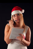 Christmas girl. Christmas blonde girl with pencil and bloc notes thinking and writing stock photography