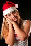 Christmas girl. Gesticulated Christmas blonde girl like reposing, black background royalty free stock image