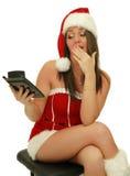 Christmas girl. Emotional beautiful christmas girl wearing santa hat, holding calculator royalty free stock image
