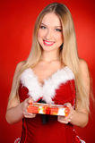 Christmas girl. A girl in a red dress with a gift in hand on a red background Stock Photo