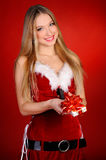 Christmas girl. A girl in a red dress with a gift in hand on a red background Stock Photos