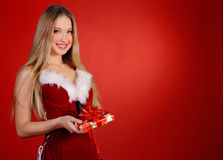 Christmas girl. A girl in a red dress with a gift in hand on a red background Royalty Free Stock Photography