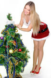 Christmas girl. The girl in red and white dress with a gift in hand next to Christmas tree Stock Photos