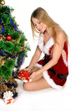 Christmas girl. The girl in red and white dress with a gift in hand next to Christmas tree Royalty Free Stock Photography