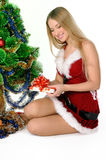 Christmas girl. The girl in red and white dress with a gift in hand next to Christmas tree Royalty Free Stock Images