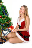 Christmas girl. The girl in red and white dress with a gift in hand next to Christmas tree Stock Photo