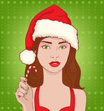 Christmas girl. Attractive brunette in a Christmas hat with lollipop in hand Royalty Free Stock Photos