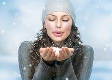 Christmas Girl. Winter woman Blowing Snow stock photo