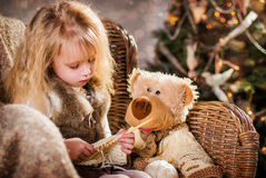 Christmas. Girl and bear sitting in a chair and knit Stock Image