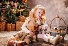 Christmas. Girl and bear sitting on the floor in front of the Christmas tree Royalty Free Stock Photo