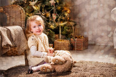 Christmas. Girl and bear sitting on the floor in front of the Christmas tree Stock Images