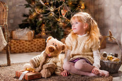 Christmas. Girl and bear sitting on the floor in front of the Christmas tree Stock Photo