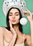 Christmas girl. Beautiful x-mas woman holding gift box and sending wind kiss over white background. stock image
