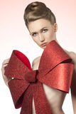 Christmas girl with big bow. Close-up christmas shoot of naked girl with elegant hair-style and big glitter red bow on her breast Royalty Free Stock Photos