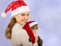 Christmas girl with a cat. Cute girl in a Christmas hat with cat royalty free stock photography