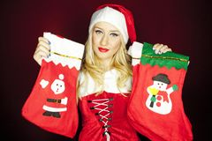 Christmas girl with Christmas stockings. Beautiful blonde model dressed in Christmas outfit holding Christmas stockings, on a red background Royalty Free Stock Photography