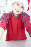 Christmas girl cooking. Smiling christmas girl cooking in kitchen Royalty Free Stock Photography