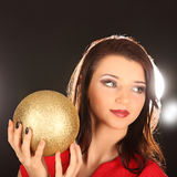 Christmas girl with cristal golden ball in her hand Royalty Free Stock Image