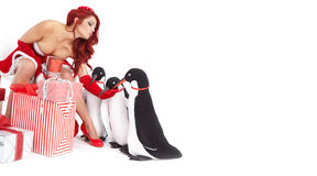 Christmas Girl in dress holding a large toy penquin. Royalty Free Stock Image