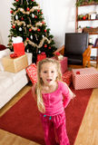 Christmas: Girl Excited on Christmas Morning. Series with a young family celebrating Christmas at home, with Christmas tree, decorations, presents, etc Royalty Free Stock Images