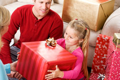 Christmas: Girl Excited To Open Big Box. Series with a young family celebrating Christmas at home, with Christmas tree, decorations, presents, etc Royalty Free Stock Photos