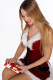 Christmas girl with gift. The girl in red and white dress with a gift in hand Stock Photography