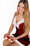 Christmas girl with gift. The girl in red and white dress with a gift in hand Stock Images