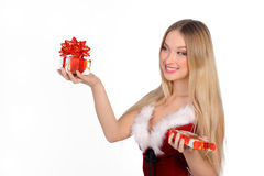 Christmas girl with gift. The girl in red and white dress with a gift in hand Royalty Free Stock Photo