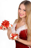 Christmas girl with gift. The girl in red and white dress with a gift in hand Royalty Free Stock Photography