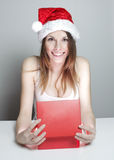 Christmas girl and gift. Surprised girl in a christmas hat with a gift Stock Photography