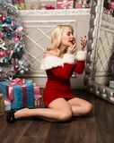 Christmas girl with gifts sitting near mirror and paints lips with lipstick. woman dressed as Santa Stock Photography