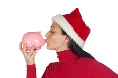 Christmas Girl giving a kiss piggy-bank Royalty Free Stock Images