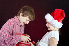Christmas girl giving present to surprised boy. Over dark Stock Photo