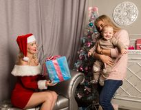 Christmas girl giving presents to little baby. woman dressed as Santa Claus. Christmas girl giving presents to little baby. women dressed as Santa Claus. family Stock Photo