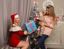 Christmas girl giving presents to little baby. woman dressed as Santa Claus. Christmas girl giving presents to little baby. women dressed as Santa Claus. family Royalty Free Stock Image