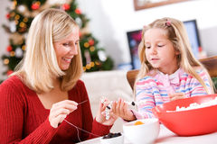 Christmas: Girl Helping Mother With Fun Popcorn Garland Decorati. Mother and child in various Christmas themed activities in the home Royalty Free Stock Photos