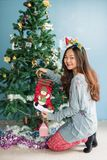 Christmas girl hide gifts in socks. Asian christmas girl hides gifts in socks to attach on Xmas tree. Attractive cute Chinese woman dressed as Santa to celebrate stock image