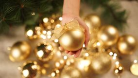 Christmas girl holding ball in hands on a background of toys. Golden ball Christmas light background stock video