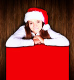 Christmas girl holding banner over wooden background Royalty Free Stock Photos
