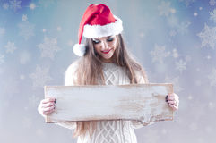 Christmas girl holding an empty wooden  board for text. Royalty Free Stock Photography