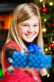 Christmas - girl holding gift and smiling Stock Images