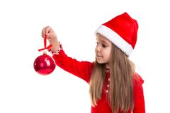 Christmas girl holding and looking at a christmas tree toy in the hand, wearing a santa hat isolated over a white royalty free stock images