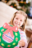 Christmas: Girl Holds Up Holiday Craft Wreath. Mother and child in various Christmas themed activities in the home Stock Image