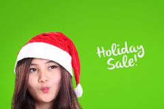 Christmas girl and Holiday Sale, closeup on green. Happy face closeup of pretty girl in Santa& x27;s hat, looking at Holiday Sale text over green background Stock Images