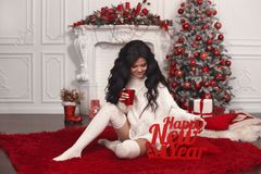 Christmas girl holidays. Happy New Year background. Beautiful br. Unette in woolen sweater and knee high socks drink hot tea over white red xmas decoration and royalty free stock photos
