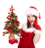 Christmas Girl In Santa Hat With Small Tree. Royalty Free Stock Image
